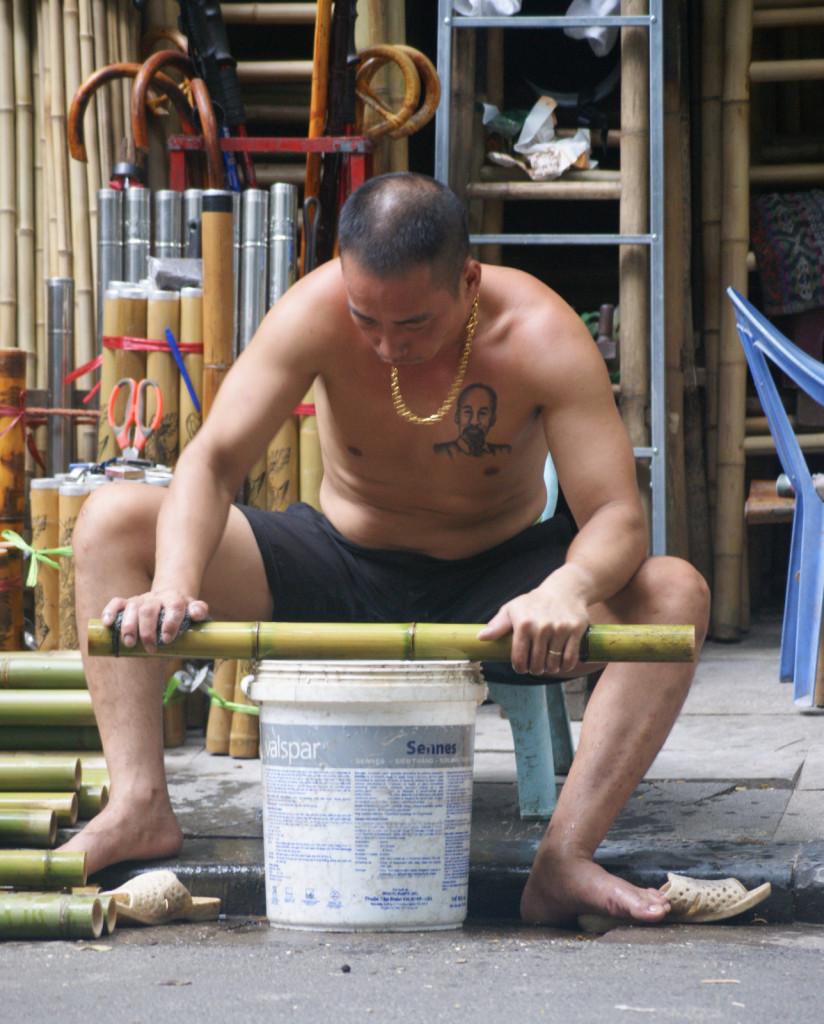 Współczesny Wietnam - pan z tatuażem z Wujkiem Ho przed swoim małym warsztatem w Hanoi